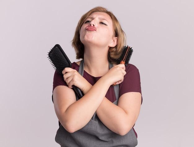 Jonge mooie vrouwenkapper in schort die haarborstels houden die handen kruisen die blazende kus opzoeken die zich over witte muur bevindt