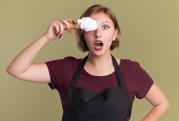 Jonge mooie vrouwenkapper in schort die scheerkwast met scheerschuim houdt die één oog behandelen die zich over groene muur bevinden
