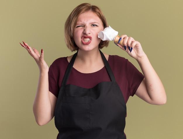 Jonge mooie vrouwenkapper in schort die scheerkwast met scheerschuim houdt die verward en ontevreden kijkt om schuim op haar gezicht te zetten dat zich over groene muur bevindt