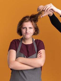 Jonge mooie vrouwenkapper in schort die voorzijde bekijkt die ontevreden en boos is omdat iemand haar haar gaat knippen dat zich over oranje muur bevindt