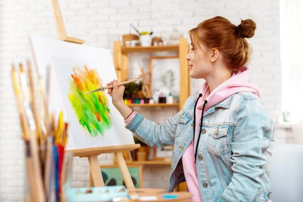 Jonge mooie vrouwenkunstenaar die het abstracte schilderen op een schildersezel trekt