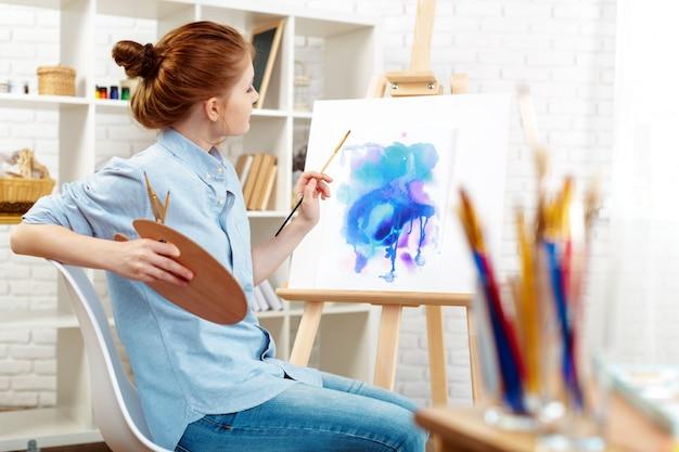 Jonge mooie vrouwenkunstenaar die het abstracte schilderen trekken op een schildersezel