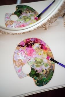 Jonge mooie vrouwenkunstenaar die thuis roze pioenen schilderen