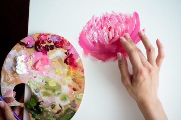 Jonge mooie vrouwenkunstenaar die thuis roze pioenen schildert
