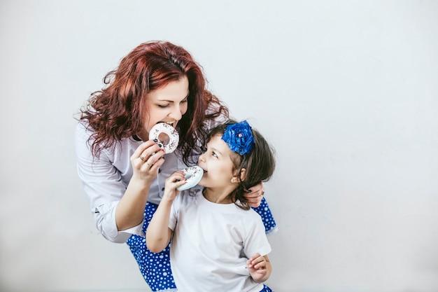 Jonge mooie vrouwenmoeder en dochter met stuk speelgoed een zoete gelukkige close-upportretten