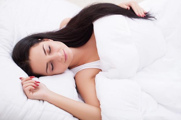 Jonge mooie vrouwenslaap in de slaapkamer. detailopname.