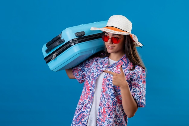 Jonge mooie vrouwentoerist die de zomerhoed en rode zonnebril draagt die reiskoffer houdt die vrolijk met vinger ernaar richt die zich over geïsoleerde blauwe achtergrond bevindt