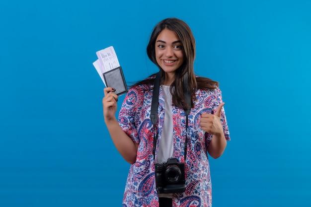Jonge mooie vrouwentoerist met het paspoort van de cameraholding met kaartjes die vrolijk glimlachen, tonend duimen, klaar aan vakantie over geïsoleerde blauwe muur