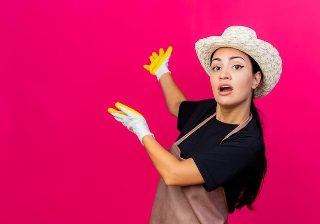 Jonge mooie vrouwentuinman die in rubberen handschoenen schort en hoed iets terug met wapens voorstelt die zich over roze muur bevinden