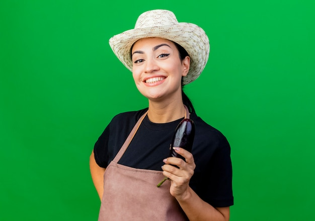 Jonge mooie vrouwentuinman die in schort en hoed die aubergine houden die voorzijde glimlachend met gelukkig gezicht bekijken die zich over groene muur bevinden