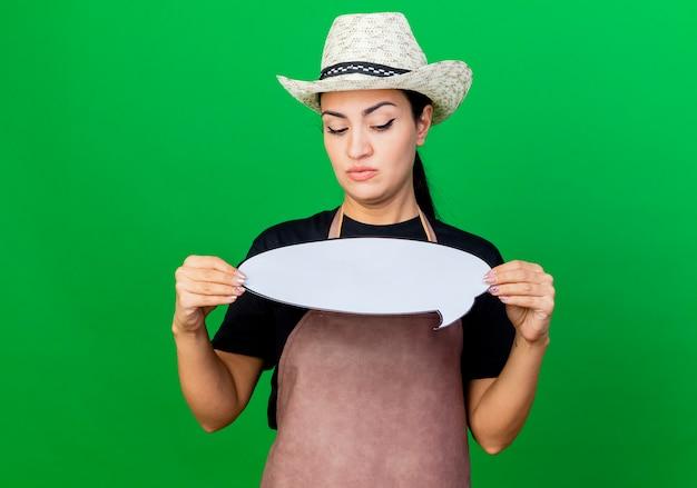 Jonge mooie vrouwentuinman die in schort en hoed het lege teken van de toespraakbel houden die het met ernstig gezicht bekijkt dat zich over groene muur bevindt