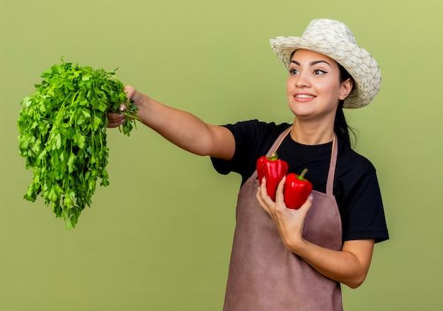Jonge mooie vrouwentuinman die in schort en hoed rode paprika's en verse kruiden houden die vrolijk status over lichtgroene muur glimlachen
