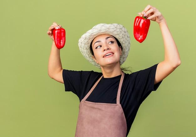 Jonge mooie vrouwentuinman die in schort en hoed rode paprika's houden die vrolijk status over lichtgroene muur glimlachen