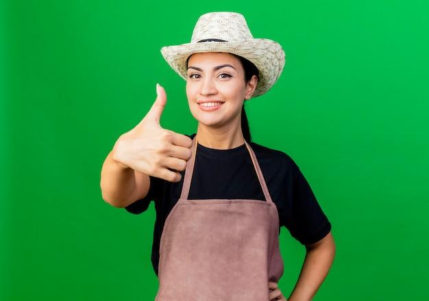 Jonge mooie vrouwentuinman die in schort en hoed voorzijde het glimlachen bekijkt die duimen toont die zich over groene muur bevinden