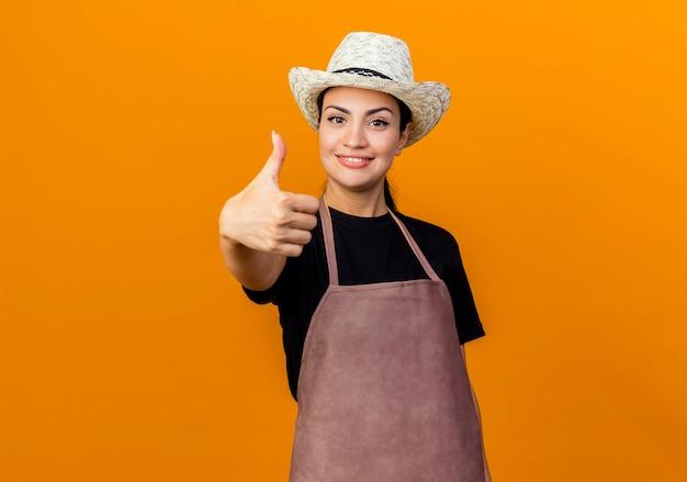 Jonge mooie vrouwentuinman die in schort en hoed voorzijde het glimlachen bekijkt die duimen toont die zich over oranje muur bevinden