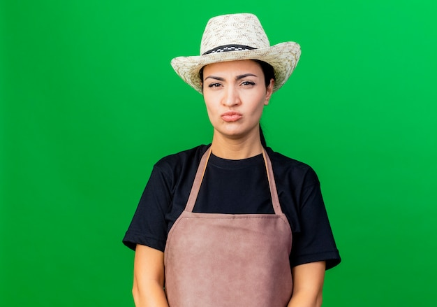Jonge mooie vrouwentuinman die in schort en hoed voorzijde met ernstig gezicht bekijkt dat zich over groene muur ontevreden bevindt