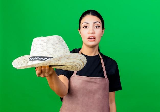 Jonge mooie vrouwentuinman die in schort haar hoed toont die voorzijde met ernstig gezicht bekijkt dat zich over groene muur bevindt