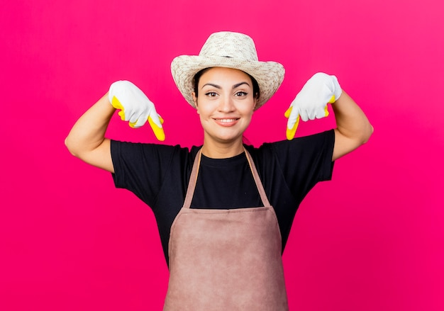 Jonge mooie vrouwentuinman in rubberhandschoenenschort en hoed die met wijsvingers naar beneden glimlachen die status over roze muur richten