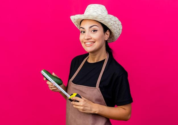Jonge mooie vrouwentuinman in schort en hoed die aubergine en meetlint houden die voorzijde met gelukkig gezicht bekijken die zich over roze muur bevinden