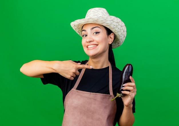Jonge mooie vrouwentuinman in schort en hoed die aubergine houden die met wijsvinger richten op het glimlachend status over groene muur