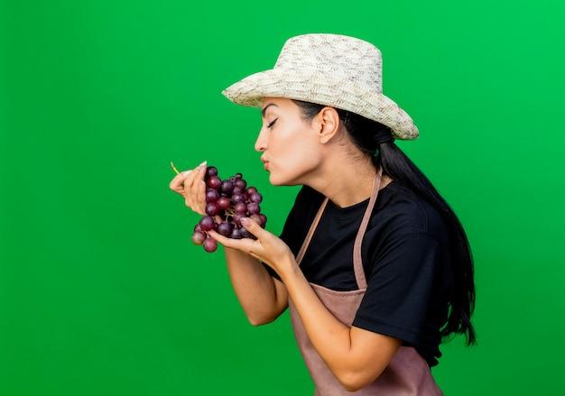 Jonge mooie vrouwentuinman in schort en hoed die bos van druiven houdt die het die zich over groene muur kust