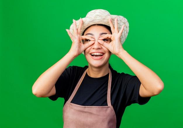 Jonge, mooie vrouwentuinman in schort en hoed die een verrekijker gebaar maakt met vingers die door vingers kijken die over groene achtergrond staan