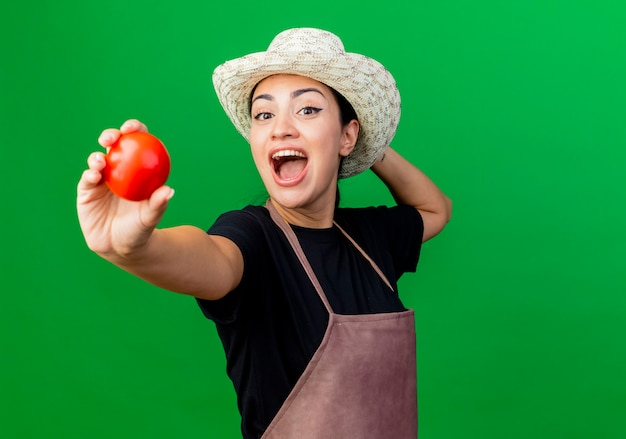 Jonge mooie vrouwentuinman in schort en hoed die hapy en opgewekte tomaten tonen die zich over groene muur bevinden