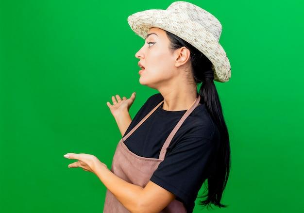 Jonge mooie vrouwentuinman in schort en hoed die iets met handen achter haar voorstellen