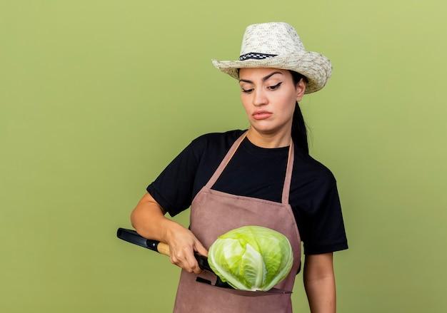 Jonge mooie vrouwentuinman in schort en hoed die kool op een schop houden die het met ernstig gezicht bekijkt dat zich over lichtgroene muur bevindt