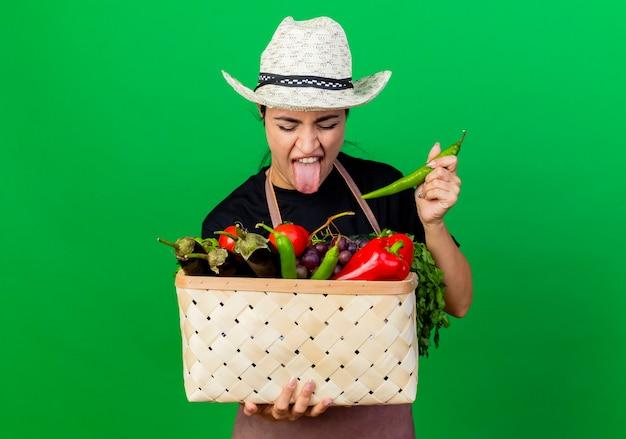 Jonge mooie vrouwentuinman in schort en hoed die mand vol groenten en groene chilipeper houdt die het met walgelijke uitdrukking bekijkt die zich over groene muur bevindt