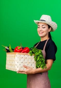 Jonge mooie vrouwentuinman in schort en hoed die mandhoogtepunt van groenten houden die met gelukkig gezicht glimlachen die zich over groene muur bevinden