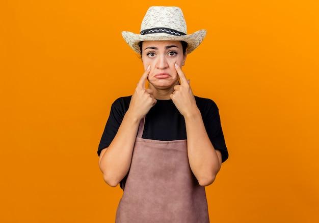 Jonge mooie vrouwentuinman in schort en hoed die naar voorkant kijkt wijzend met vingers naar haar ogen met droevige uitdrukking huilen staande over oranje muur
