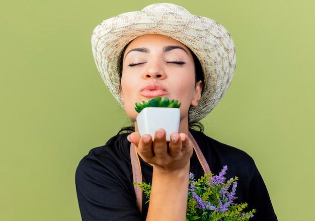 Jonge mooie vrouwentuinman in schort en hoed die potplanten toont die een kus blazen die zich over lichtgroene muur bevindt