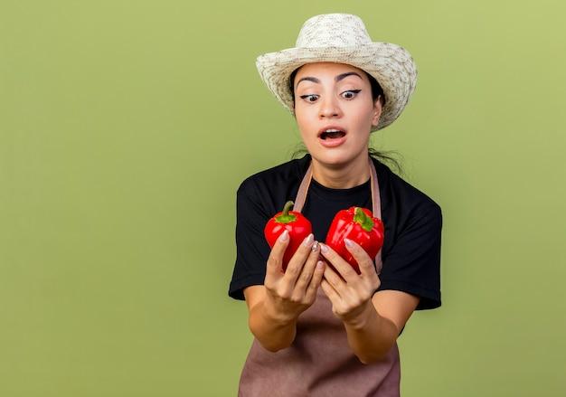 Jonge mooie vrouwentuinman in schort en hoed die rode paprika houdt die hen bekijkt terwijl hij verrast en verbaasd over de lichtgroene muur staat