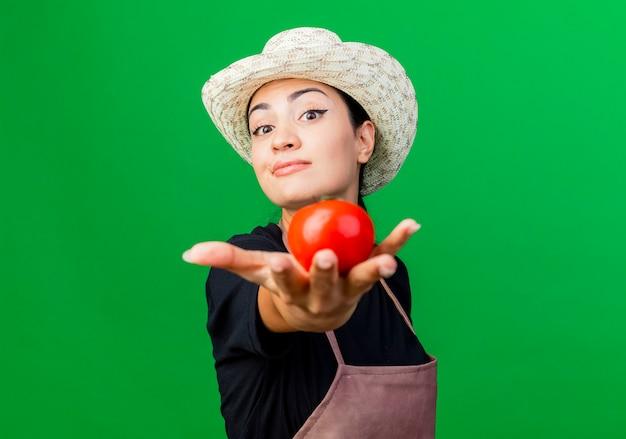 Jonge mooie vrouwentuinman in schort en hoed die tomaat glimlachen die zekere status over groene muur glimlachen