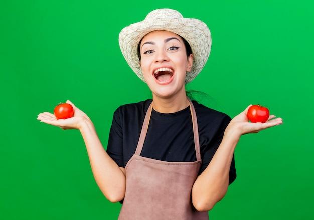 Jonge, mooie vrouwentuinman in schort en hoed die tomaten vasthoudt die glimlachen met een blij gezicht dat over een groene achtergrond staat