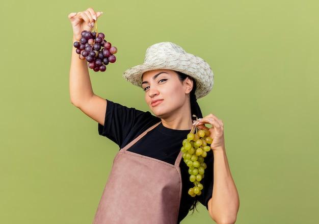 Jonge mooie vrouwentuinman in schort en hoed die trossen druiven houden die voorzijde met ernstig gezicht bekijken die zich over lichtgroene muur bevinden