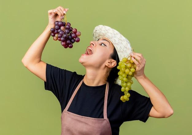 Jonge mooie vrouwentuinman in schort en hoed die trossen druiven houdt met wijd openende mond die druif gaat eten die zich over lichtgroene muur bevindt