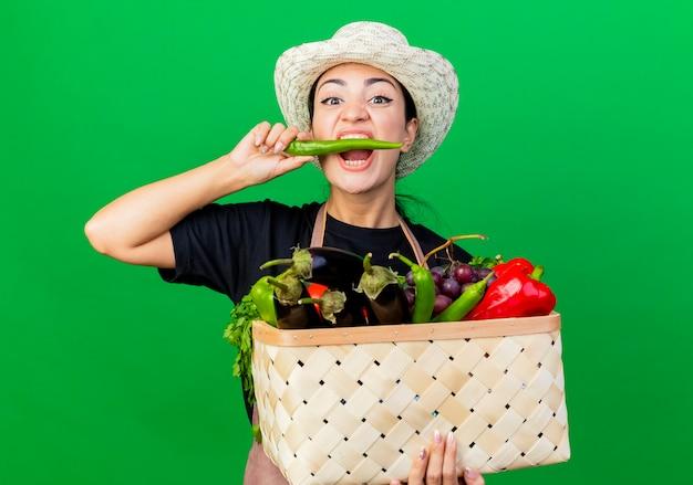 Jonge mooie vrouwentuinman in schort en hoedenholding mandhoogtepunt van groenten die groene spaanse peperpeper bijten die zich over groene muur bevinden