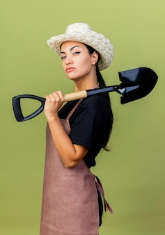 Jonge mooie vrouwentuinman in schort en hoedenholding schop die voorzijde met ernstig gezicht bekijkt dat zich over lichtgroene muur bevindt