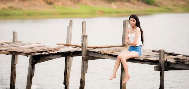 Jonge mooie vrouwenzitting alleen op de pijler