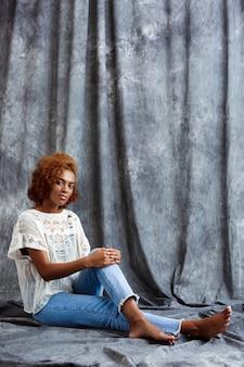 Jonge mooie vrouwenzitting bij vloer over grijze muur