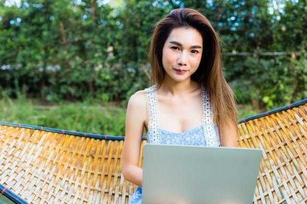 Jonge mooie vrouwenzitting in bamboehangmat die laptop met behulp van