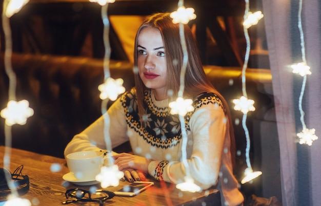 Jonge mooie vrouwenzitting in koffie, het drinken koffie. kerstmis, nieuwjaar, valentijnsdag, wintervakantie