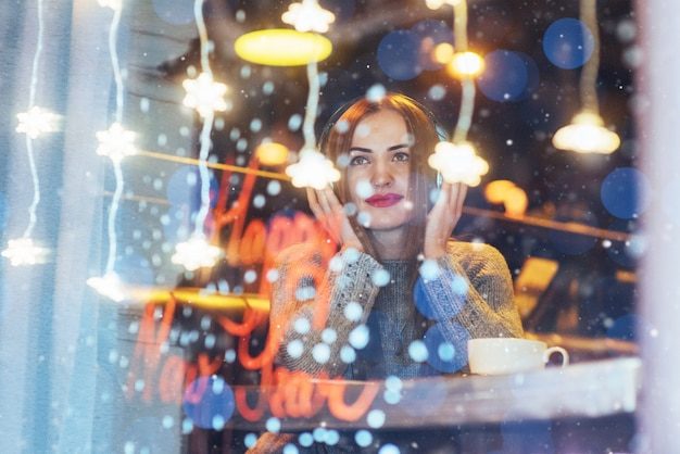 Jonge mooie vrouwenzitting in koffie, het drinken koffie. model luisteren naar muziek.