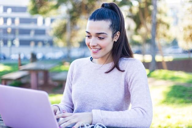 Jonge mooie vrouwenzitting in openlucht terwijl het werken met laptop