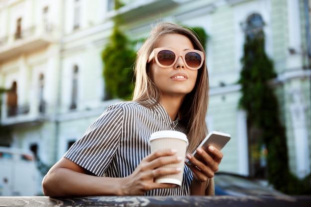 Jonge mooie vrouwenzitting op bank, die koffie en telefoon houdt.