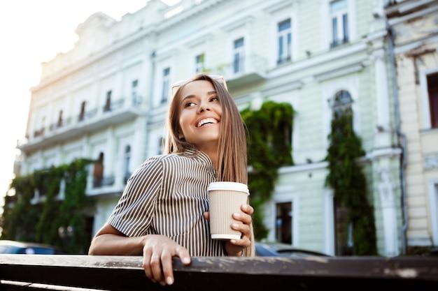 Jonge mooie vrouwenzitting op bank, die koffie, het glimlachen houdt.