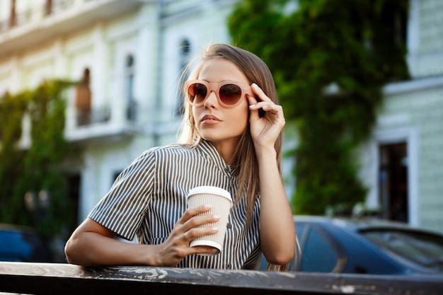 Jonge mooie vrouwenzitting op bank, die koffie houdt.