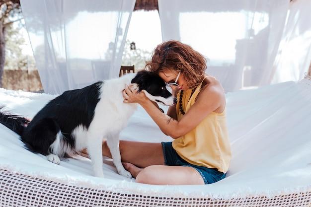 Jonge mooie vrouwenzitting op hangmat met haar border collie-hond in openlucht